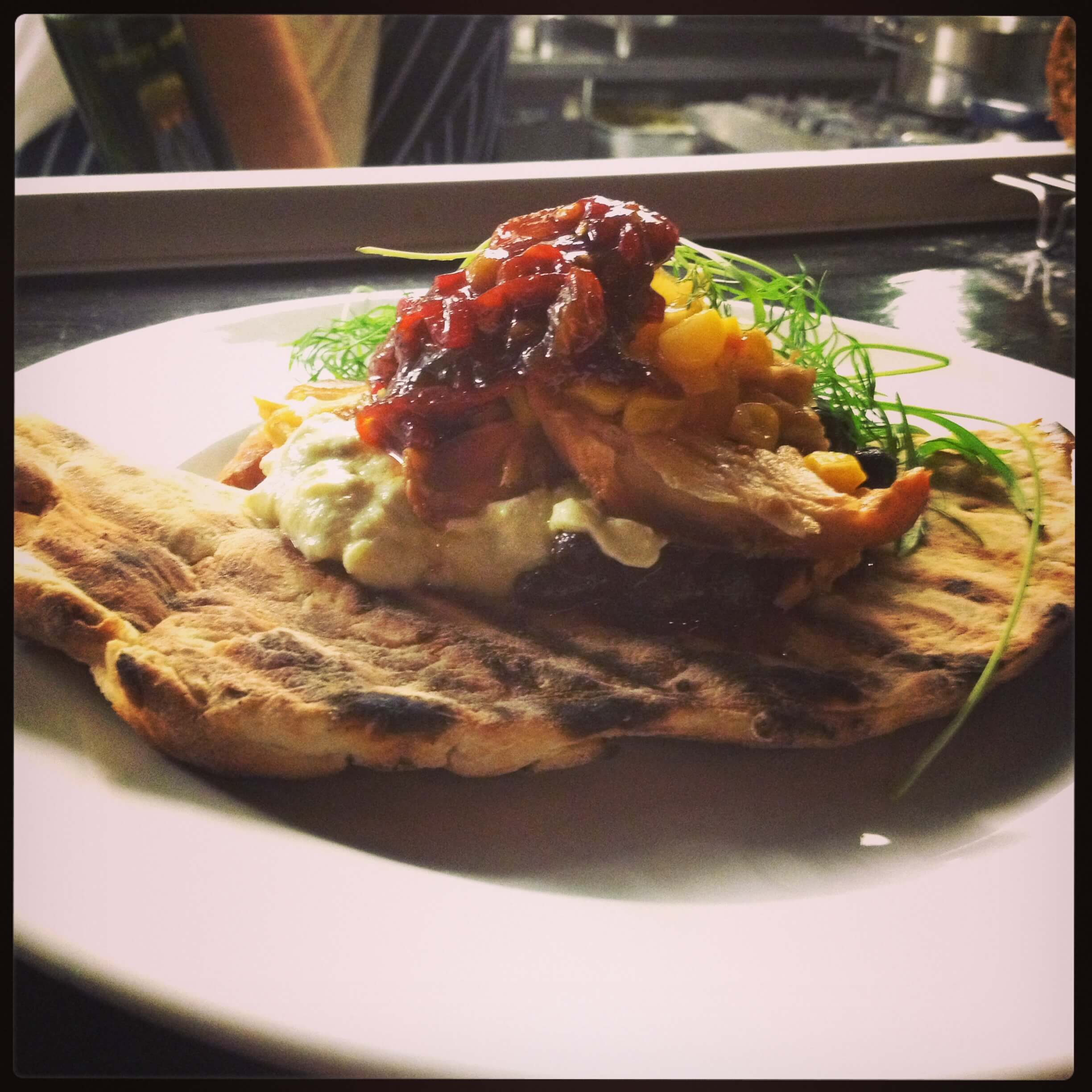 Pulled rabbit with smoked black beans, sweetcorn and pineapple relish, avocado and sour cream flatbread