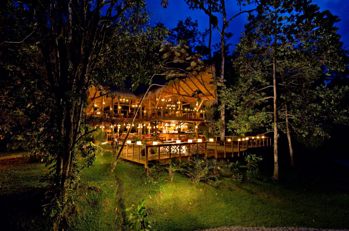 A wooden lodge lit with candles on a green hillside in Costa Rica