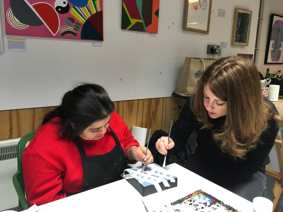 Two artists working on a piece in a studio