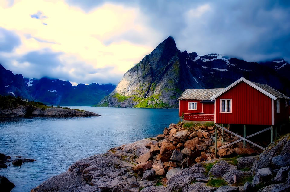 A red house on stilts looks over blue water in Norway, with mountains in the distance